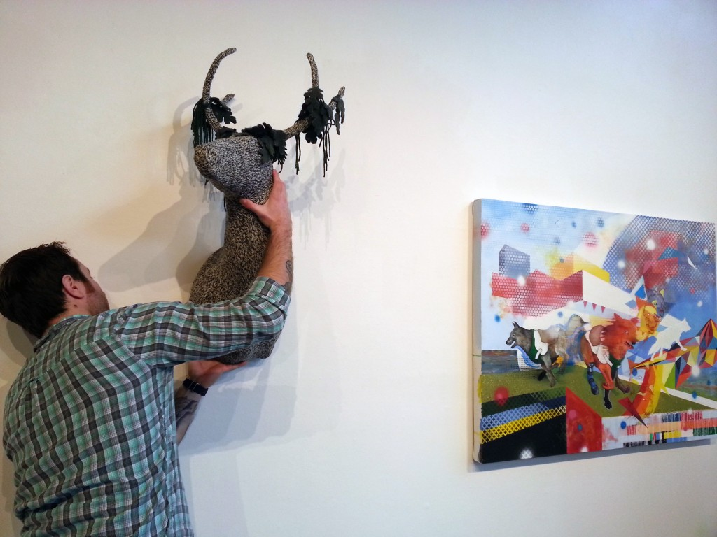 Grant Barber, UW Museuology Program Emerging Curator Initiative Gallery Intern, hangs Imaginature show
